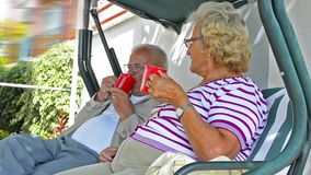 Senior couple resting and drinking coffee. Senior couple sitting together talking, resting and having daily tea, coffee- Stock Video. Mature retired couple stock footage