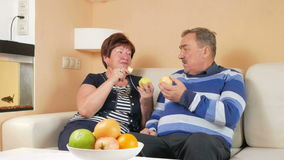 Senior couple resting at home on the couch and eat apples. On the table is a plate of different fruits. The husband and stock video footage