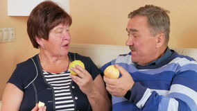 Senior couple resting at home on the couch and eat apples. On the table is a plate of different fruits. The husband and stock video