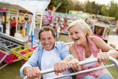 Senior couple on a ride in amusement park. Senior couple having fun on a ride in amusement park. Summer vacation Stock Image