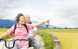 Senior  Couple Riding Bicycle on country road Stock Images