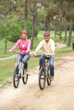 Senior couple riding bicycle in park Royalty Free Stock Photography