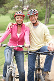 Senior couple riding bicycle in park Stock Images