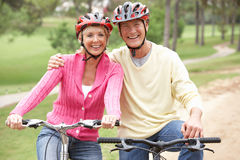 Senior couple riding bicycle in park Stock Photos