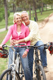 Senior couple riding bicycle in park. Looking forward smiling stock photo