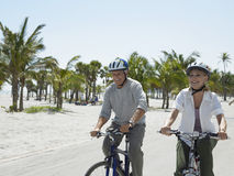 Senior Couple Riding Bicycles On Beach Royalty Free Stock Images