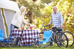 Senior Couple Riding Bikes On Camping Holiday. In Countryside Stock Photo