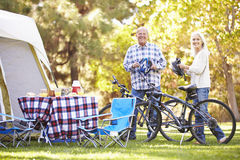 Senior Couple Riding Bikes On Camping Holiday. In Countryside Smiling To Camera Stock Image