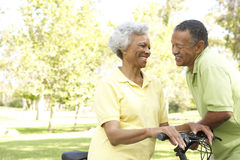 Senior Couple Riding Bikes In Park Stock Photos