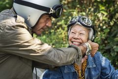 Senior couple riding a classic scooter royalty free stock photo