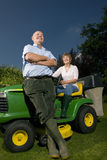 Senior couple and riding lawn mower stock image