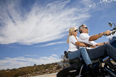 Senior couple riding motorcycle on desert road Royalty Free Stock Photography