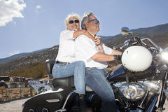 Senior couple riding a motorcycle together in a rural landscape Stock Photography