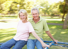 Senior Couple Riding On Roundabout In Park. Having Fun Royalty Free Stock Photo