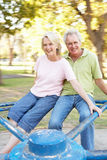 Senior Couple Riding On Roundabout In Park. Having Fun Stock Photo