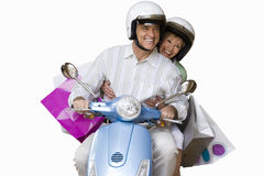 Senior couple riding on scooter, cut out stock images