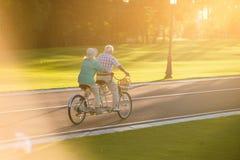 Senior couple riding tandem bicycle. Stock Photo