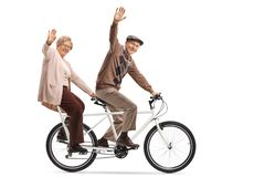 Senior couple riding a tandem bycicle and waving stock images