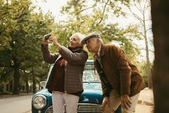 Senior couple on road trip taking pictures. Of nature landscape with digital camera. Old women taking photographs with her camera with men standing by and royalty free stock photos