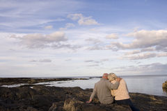 Senior couple on rocks looking out to sea, man with arm around woman, rear view Stock Photos