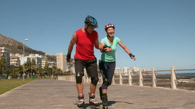 Senior couple roller blading along the pier stock video footage
