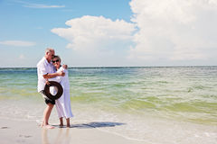 Senior couple romance. An elderly couple hugging on a tropical beach royalty free stock images