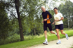 Senior Couple Running. Active senior couple running in the woods Royalty Free Stock Images