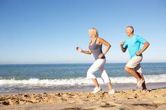 Senior Couple Running Along Beach royalty free stock image