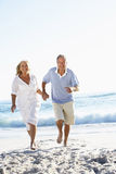 Senior Couple Running Along Beach Royalty Free Stock Photos