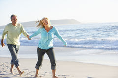 Senior Couple Running Along Beach stock images