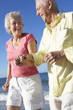 Senior Couple Running Along Beach Together Stock Images