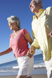 Senior Couple Running Along Beach Together Royalty Free Stock Images