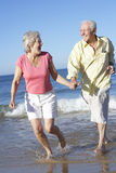 Senior Couple Running Along Beach Together Royalty Free Stock Image