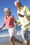Senior Couple Running Along Beach Together Stock Photos