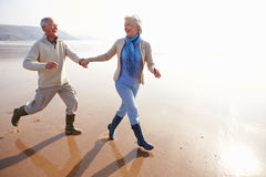 Senior Couple Running Along Winter Beach Stock Photography
