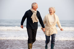 Senior Couple Running Along Winter Beach stock images
