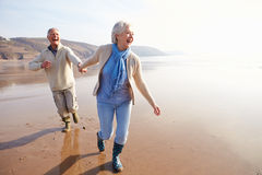 Senior Couple Running Along Winter Beach Royalty Free Stock Photography
