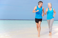 Senior Couple Running On Beautiful Beach Royalty Free Stock Image