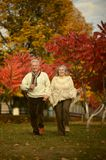 Senior couple running in park. Senior couple running in casual clothing in park Royalty Free Stock Photos