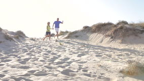 Senior Couple Running Down Sand Dune Together. Senior couple in casual clothing running down sand dune and past camera position. Shot on Canon 5d Mk2 with a stock video footage