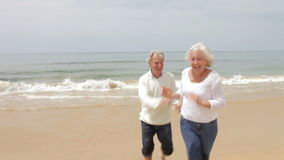 Senior Couple Running On Fall Beach. Senior man chases wife along beach towards camera as she laughs.Shot on Canon 5D Mk2 at at a frame rate of 25 fps stock video footage