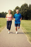 Senior couple running. stock photos
