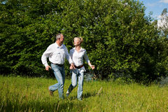 Senior Couple running on a meadow. Very active mature or senior couple running over the grass on a meadow in summer Royalty Free Stock Photography