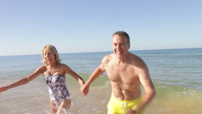 Senior Couple Running Out Of The Sea Holding Hands. Senior couple run out of sea towards camera holding hands.Shot on Canon 5d Mk2 with a frame rate of 30fps stock footage