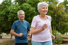 Senior couple running outdoor. Senior couple running outside at park. Elderly men and old women jogging together. Retired men and active women exercising outdoor royalty free stock images
