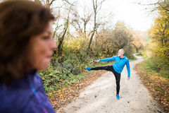 Senior couple running outside in sunny autumn forest, stretching. Beautiful active senior couple running together outside in sunny autumn forest, stretching Stock Photos