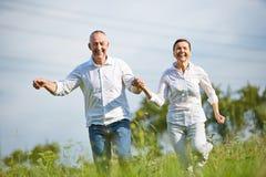 Senior couple running over meadow. Happy senior couple running over meadow in summer Stock Photo