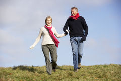 Senior Couple Running In The Park. Wearung Winter Clothes Stock Photo