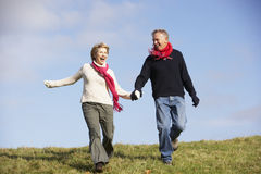 Senior Couple Running In The Park. Wearung Winter Clothes Stock Photos