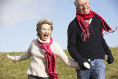 Senior Couple Running In The Park. Wearung Winter Clothes Royalty Free Stock Photo